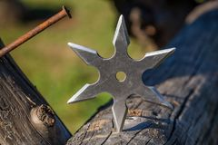 Shuriken throwing star, traditional japanese ninja cold weapon. Stuck in wooden background royalty free stock images
