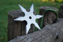 Shuriken throwing star, traditional japanese ninja cold weapon. Stuck in wooden background royalty free stock photo
