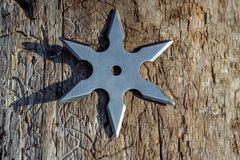 Shuriken throwing star, traditional japanese ninja cold weapon. Stuck in wooden background stock photos