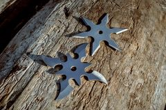Shuriken throwing star, traditional japanese ninja cold weapon stuck in wooden background.  stock images