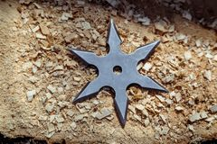 Shuriken throwing star, traditional japanese ninja cold weapon stuck in wooden background.  stock photo