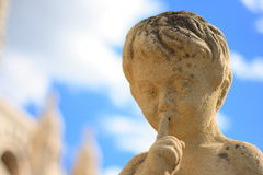 Shush!. A statue of a boy against blue sky Royalty Free Stock Photo