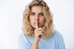 Shush you cannot say it. Portrait of displeased blond girl with short haircut and blue eyes looking with dismay frowning. Saying shh with index finger on mouth stock photos