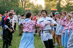 Couple in colorful folk costumes, dancing in a crowd for the time of the annual Intl festival. SHUSHENSKOE, RF - July 12, 2014: Couple in colorful folk costumes royalty free stock photo