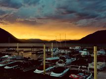 Shuswap Storm. A storm brews on the Shuswap Lake in Salmon Arm, BC as seen by the golden cloudy sky reflected in the water as dark boats float unaware tethered royalty free stock photography