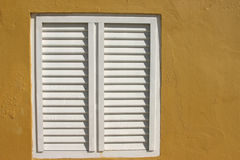 Shut. White shutters of yellow building royalty free stock images