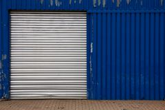 Shut Door on Blue Metal Shed. Closed door on a worn blue industrial metal shed at a shipyard in Hamburg, Germany Royalty Free Stock Image