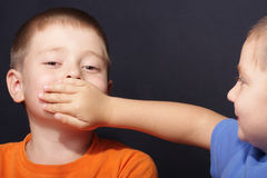 Shut up. Boy shuts brother's mouth by palm over dark background Royalty Free Stock Image
