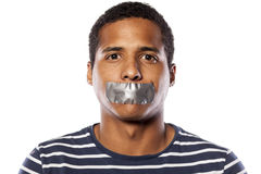 Shut up mouth. Dark-skinned young man with adhesive tape over his mouth royalty free stock photos