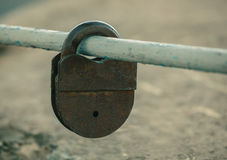 Shut up, old, worn, rusty, shabby padlock hanging on painted, worn, cut, pipe Royalty Free Stock Images