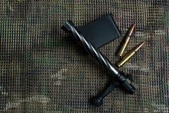 Shutter, agrafe de carabine, les munitions, mensonges et sur le fond de modèle de multicam Image stock