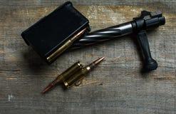 Shutter, clip della carabina, le munizioni, bugie e su un fondo di legno Immagine Stock