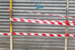 Shutter door closed with caution tape Royalty Free Stock Image