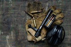 Shutter, grampo da carabina, munição, luvas e mentiras dos fones de ouvido da proteção de orelha no fundo do multicam Fotografia de Stock Royalty Free