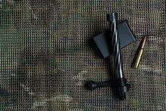 Shutter, grampo da carabina, munição, mentiras e no fundo do teste padrão do multicam Imagem de Stock Royalty Free