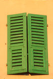 Shuttered window. Typical wooden green shutters on a pastel background in Italy Stock Image