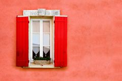 Shuttered window against red stone wall. Red shuttered window against red ocher colored wall Stock Photos