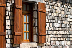 Shuttered window on stone wall Royalty Free Stock Photos