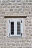 Shuttered window in a stone wall of a house close-up Stock Photos