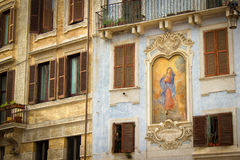 Shutters and Windows with Balconies and Historic Painted Religious Mural on Apartments in Rome, Italy. Royalty Free Stock Photography