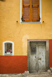 Wood Shutters and Windows and Wooden Doorway with Yellow and Orange Apartment in Cinque Terre Italy. An orange and yellow apartment home in the Cinque Terre Royalty Free Stock Photos