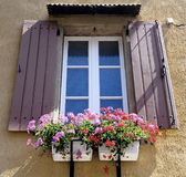 Shutters. With flower pots filled with geraniums in main square of french town Stock Images