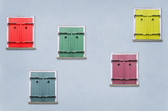 Shutters. Closed windows with colorful shutters in the blue house wall Royalty Free Stock Image