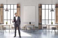 Shutters cafe interior with a poster, man. African American businessman in a modern cafe interior with concrete walls and floor, wooden shutters at tall windows Royalty Free Stock Photography