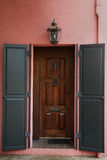 Shutters on large rich brown front door Royalty Free Stock Image
