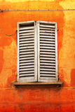 Shutters on orange wall Stock Photo