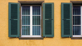 Windows and Shutters. A bright yellow building with fillet wall style with dark green shutters and blinds. Walkringen, BE Switzerland Stock Images