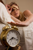 Shutting off the alarm clock. Blond woman sleeping in bed peeking out from cover over eyes looking at the clock and reaching to turn off a round gold alarm clock Stock Photos