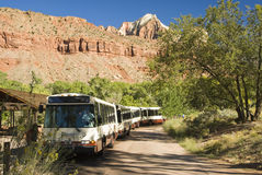 Shuttle bus 1. A porpane fueled shuttle bus stops at the Visitor's Center in Zion National Park in southwest Utah. Sandstone formations in the background Royalty Free Stock Image