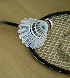 Shuttle Cock on top of a Badminton Racquet. This picture shows you a white coloured shuttle cock with a red band, sitting on top of a Badminton racquet/bat Royalty Free Stock Photography