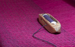Shuttle Resting on Woven Wine-Colored Fabric Royalty Free Stock Photos