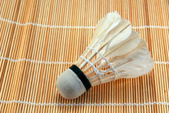 Shuttlecock against a wooden floor mat Royalty Free Stock Photo