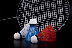 Shuttlecock and badminton racket. Over black background Royalty Free Stock Images