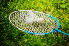 Shuttlecock and badminton racket on green grass. Shuttlecock and badminton racket on green grass royalty free stock images