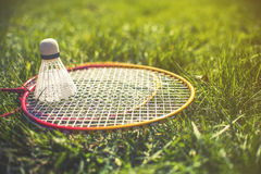 Shuttlecock and badminton racket on green grass stock image
