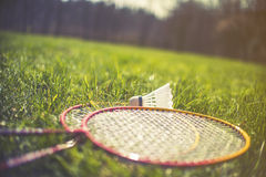 Shuttlecock and badminton racket on green grass royalty free stock photography