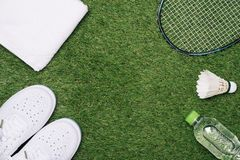 Shuttlecock and badminton racket with shoe, water and towel on grass background.  royalty free stock photography