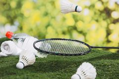 Shuttlecock and badminton racket with water and towel on the grass in the park. royalty free stock photography