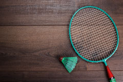 Shuttlecock and badminton racket. On wooden background Royalty Free Stock Images