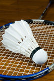 Shuttlecock with badminton racket. On the wooden court Royalty Free Stock Photography