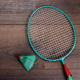 Shuttlecock and badminton racket. On wooden table after the game Royalty Free Stock Photography