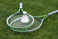 Shuttlecock on badminton rackets lying on green grass Royalty Free Stock Photos