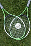 Shuttlecock on badminton rackets lying on green grass Stock Photography