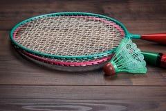 Shuttlecock and badminton rackets. Shuttlecock and badminton racket on brown wooden background Royalty Free Stock Photos