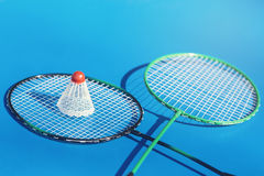 Shuttlecock or birdie on badminton racket on blue background. Sport concept. Stock Images