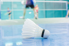 shuttlecock on the floor with badminton player Royalty Free Stock Images